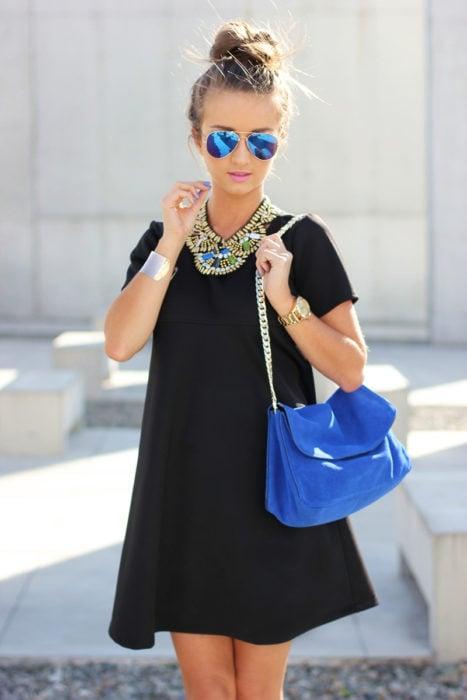 Chica usando un vestido negro y accesorios dorados