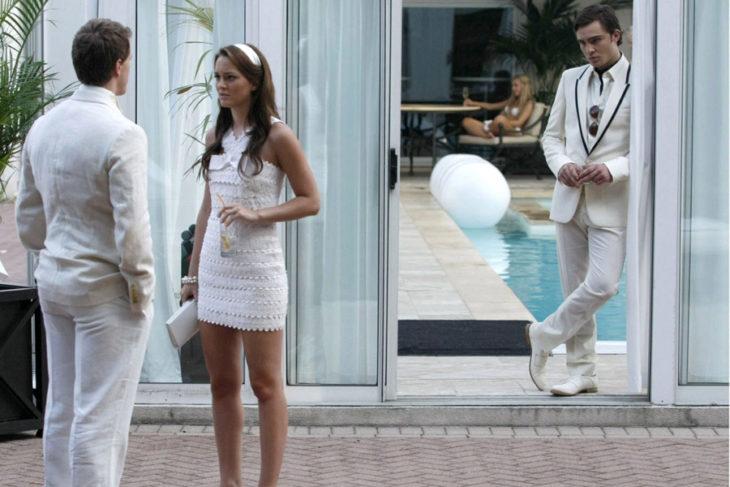 mujer con vestido blanco y hombre atras