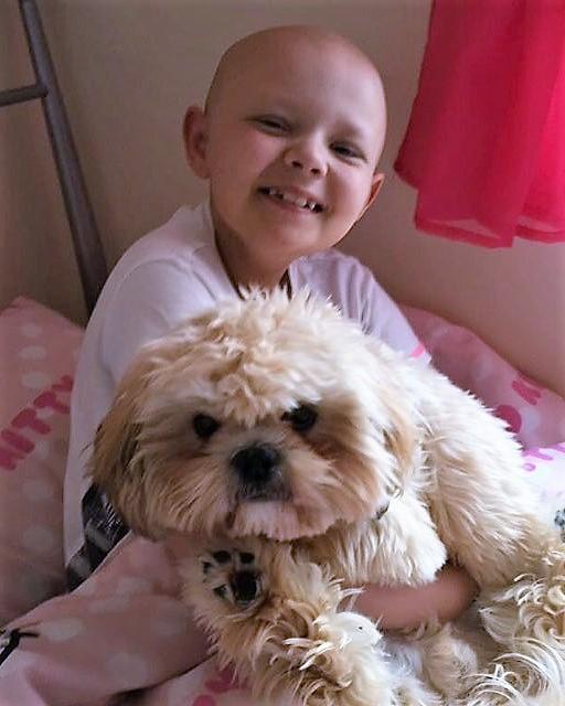 niña sin cabello con perro