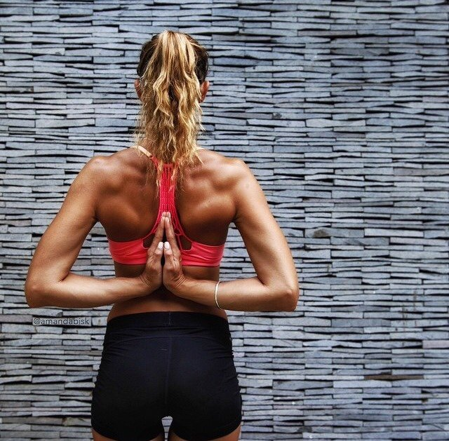 mujer rubia de espaldas haciendo yoga