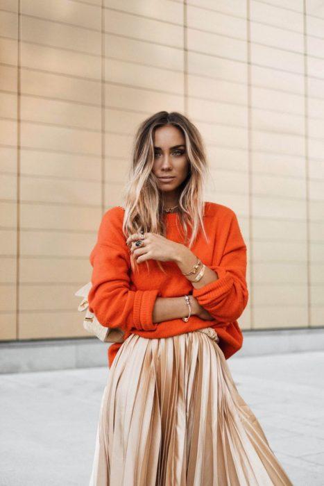 mujer rubia con sueter naranja