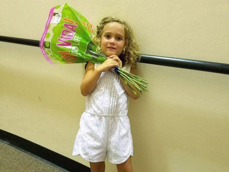 niña rubia con ramo de flores