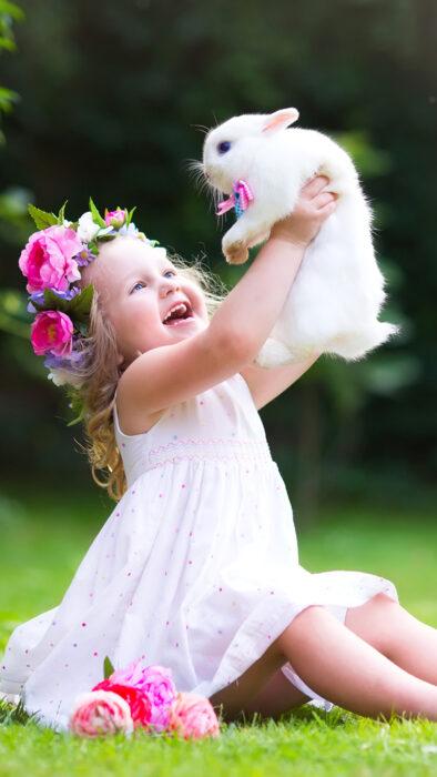 Niña sosteniendo un conejito en sus brazos mientras está sentada en el pasto