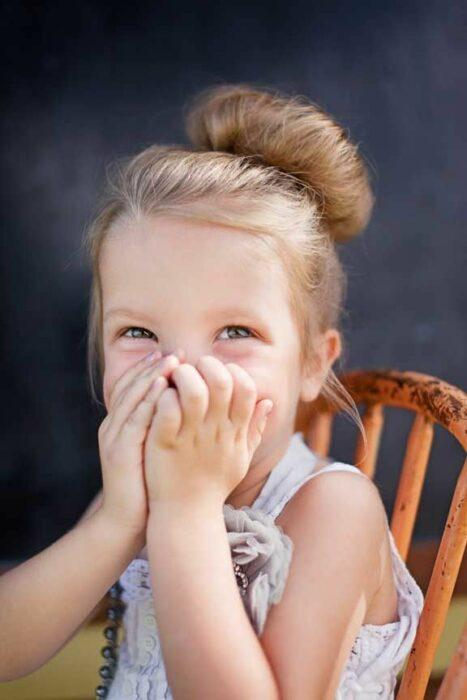 Niña sonriendo mientras cubre su boca con sus manos