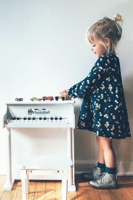 Niña jugando con sus carritos mientras están sobre un pequeño piano de juguete