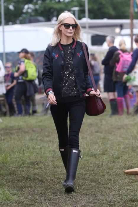 Chica usando unas botas de lluvia en el festival glastonbury