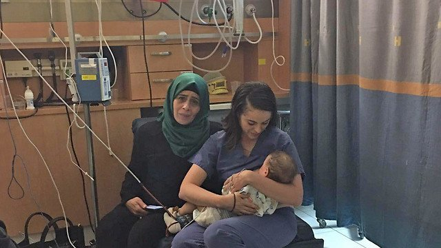 Mujer alimentando a un bebé en medio de la guerra