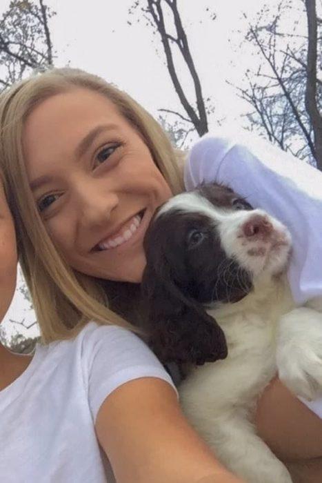 Chica sosteniendo a un perrito