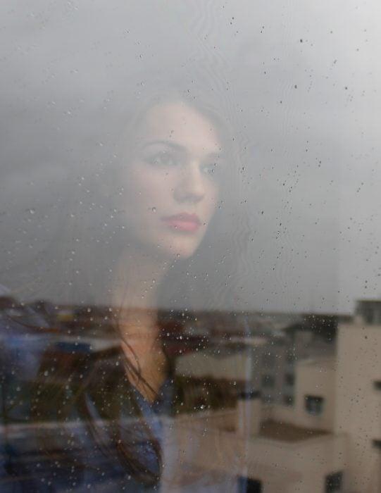 chica viendo llover