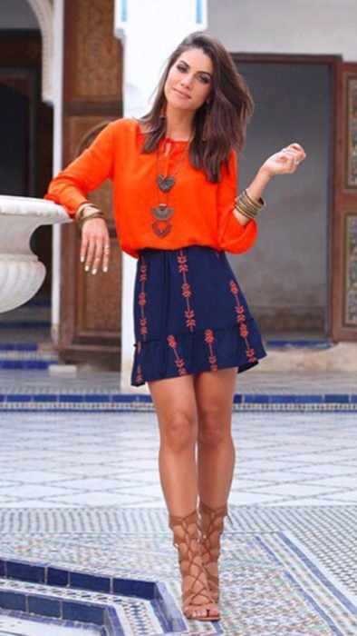 mujer con falda azul y blusa naranja