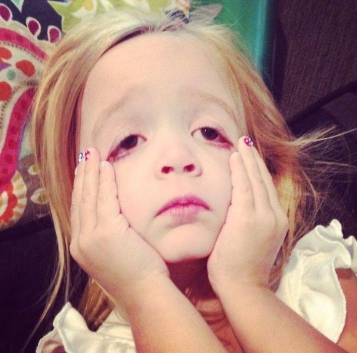 niña rubia jalando su cara