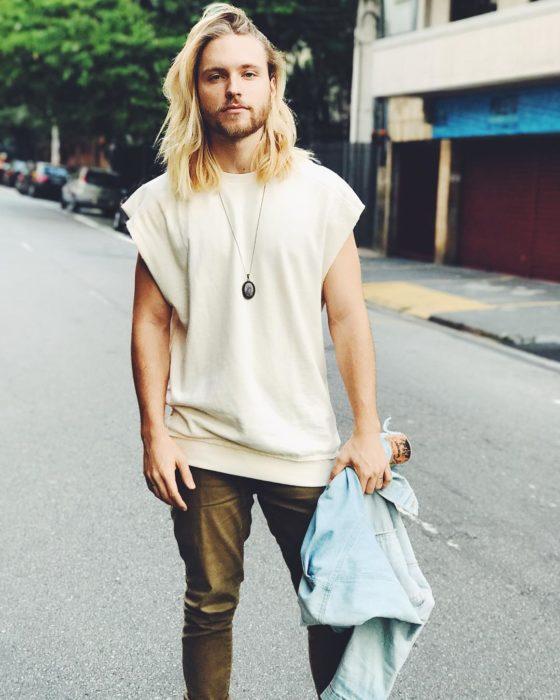 hombre rubio de cabello largo con playera blanca