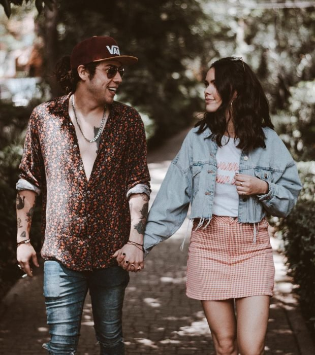 hombre rubio con lentes y gorra con mujer con falda