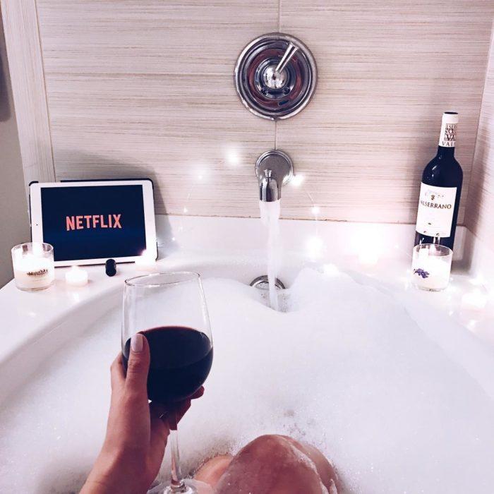 mujer en tina de baño con copa de vino