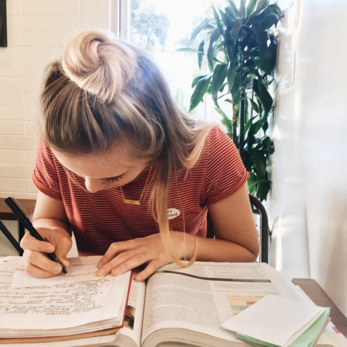 Chica escribiendo en un alibreta