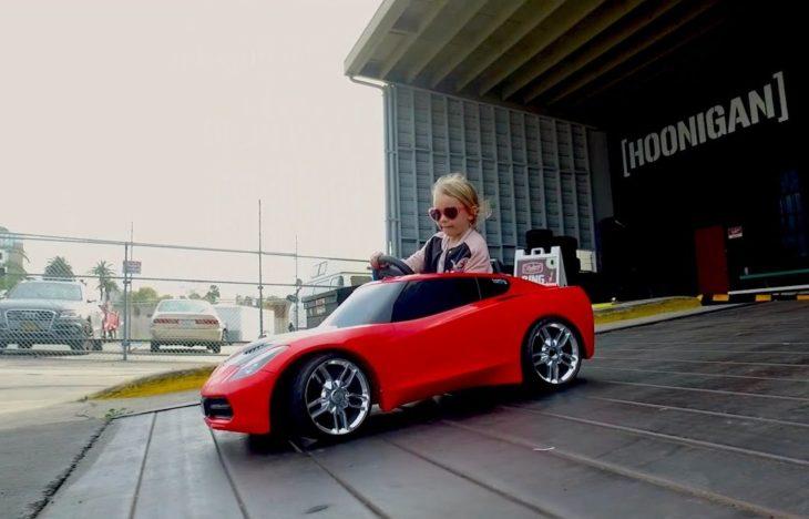 niña rubia en coche de carreras