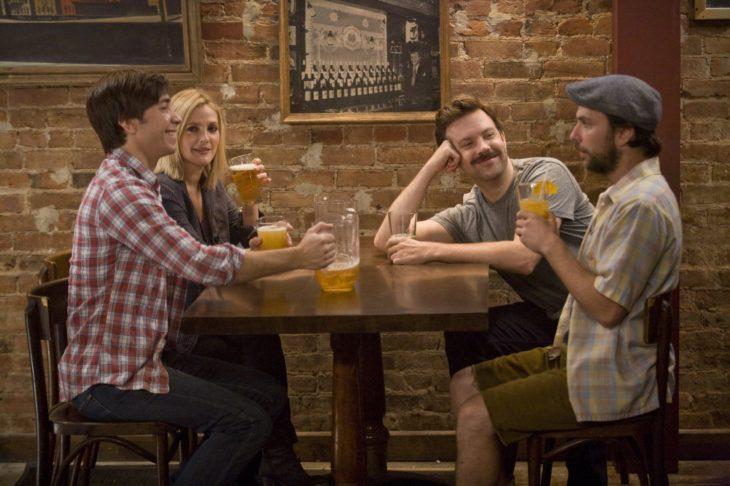 mujer con hombre y hombres en bar