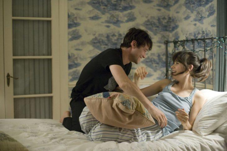 hombre y mujer sonriendo en la cama