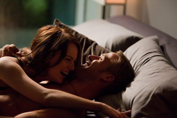hombre rubio y mujer riéndose en la cama