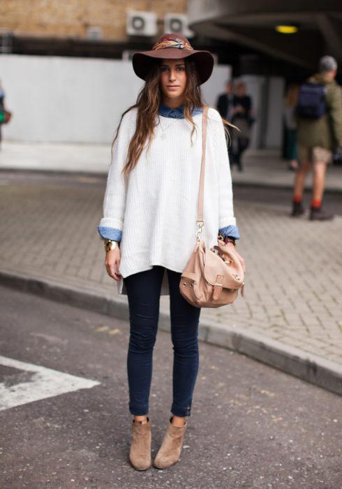 Chica usando un suéter grande y botas