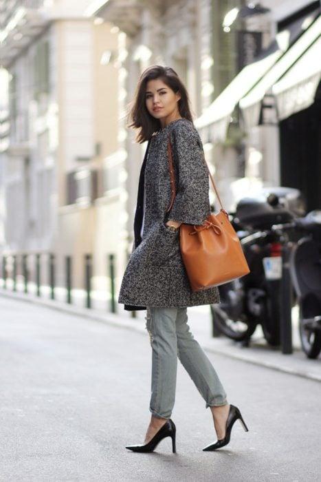 Mujer usando una bolsa color cameo
