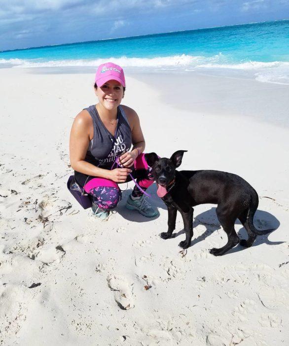 Mujer jugando con un perro en la playa