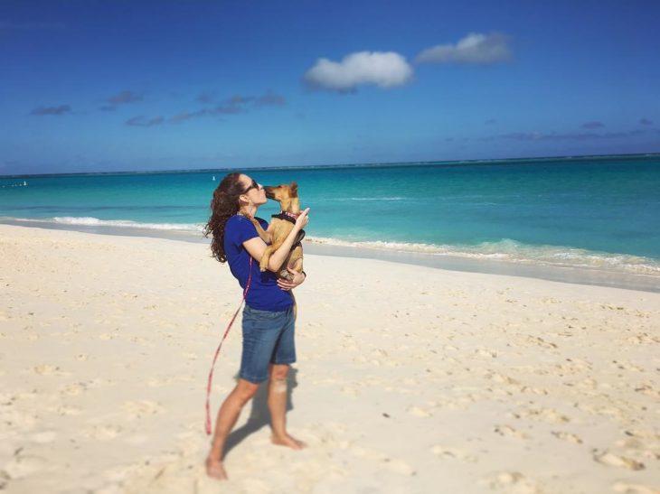 Mujer besando a un perro en la playa