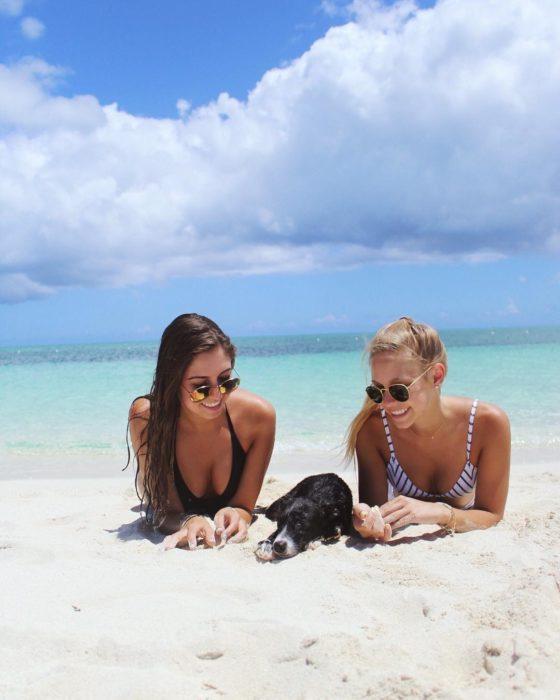 Chicas jugando en la playa con un cachorro