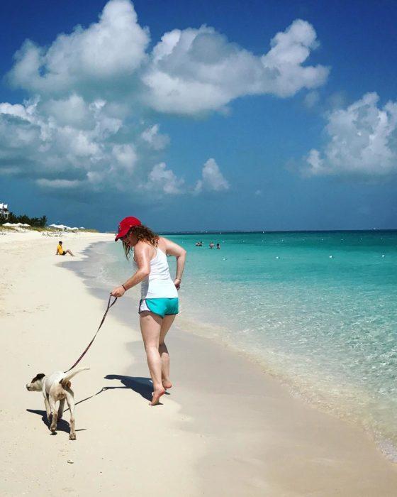 Mujer paseando a un pero en la playa