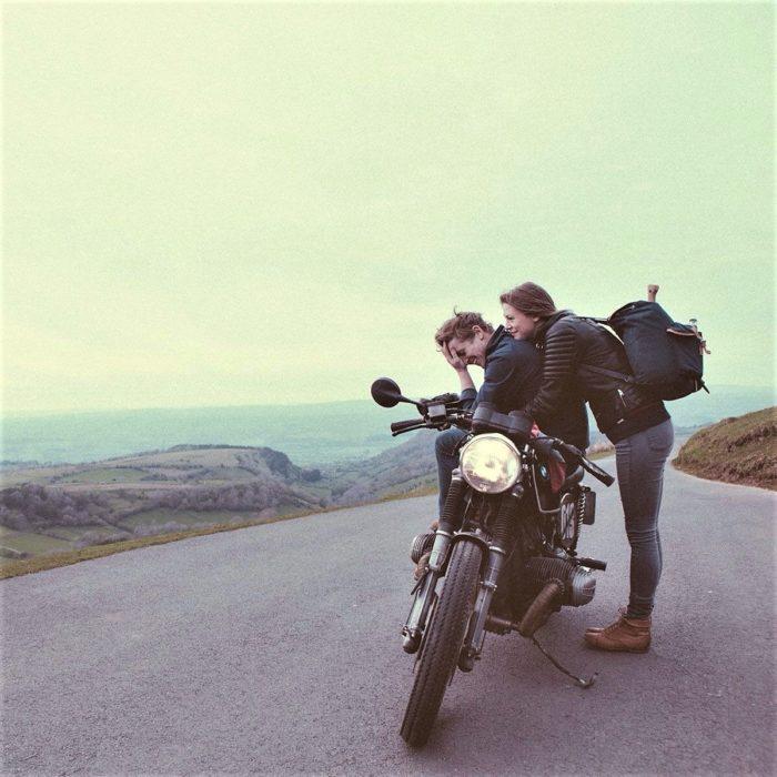 mujer y hombre con motocicleta en carretera