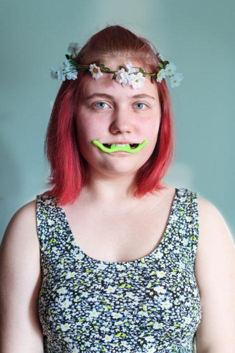 mujer con corona de flores y aparato en su boca