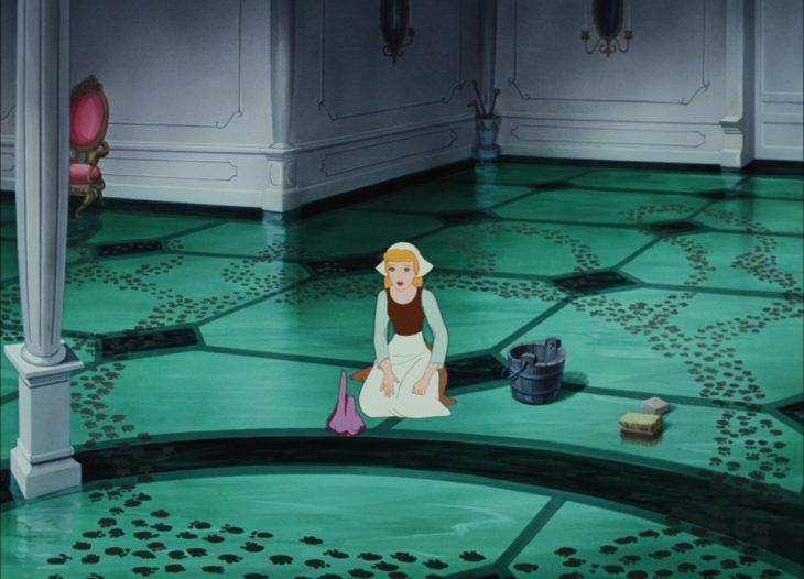 Cenicienta desanimada por tener que limpiar el piso de nuevo