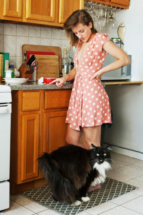 Chica en la cocina con su gato negro peludo bonito