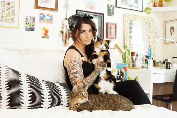Chica con un gato naranja con negro y otro gato ciego