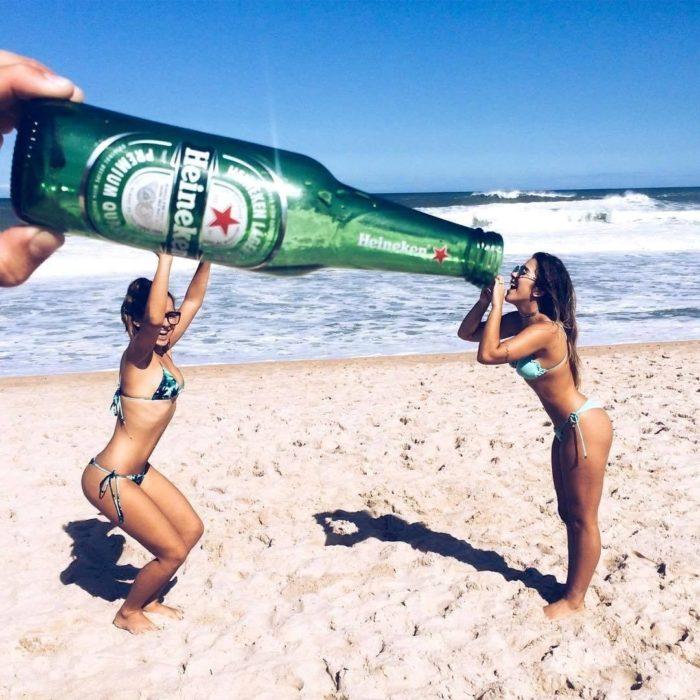 chicas sosteniendo una cerveza gigante