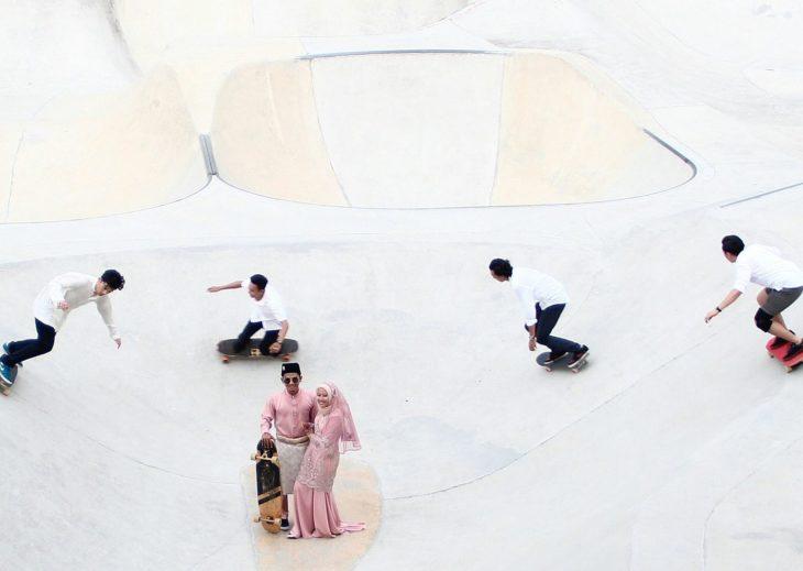 pareja de recien casados rodeada de patinadores