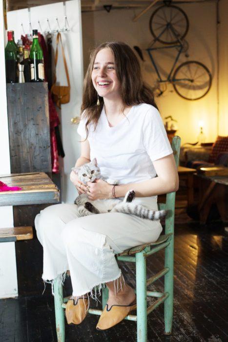 Chica con gato gris en las piernas