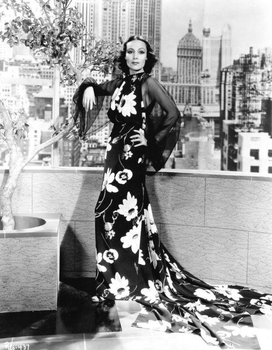 Dolores del Río usando vestido negro largo con flores blancas