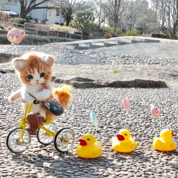 Gatito de lana en bicicleta con patos