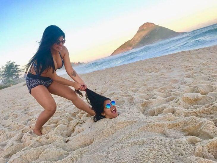 chica sacando amiga de la arena