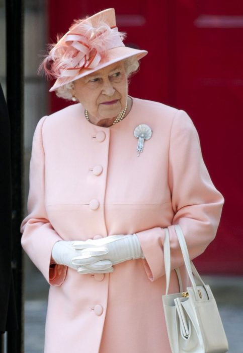 Mujer anciana reina con sombrero rosa y plumas
