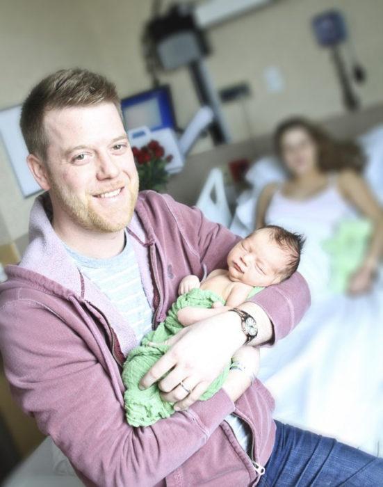 hombre rubio cargando a bebe