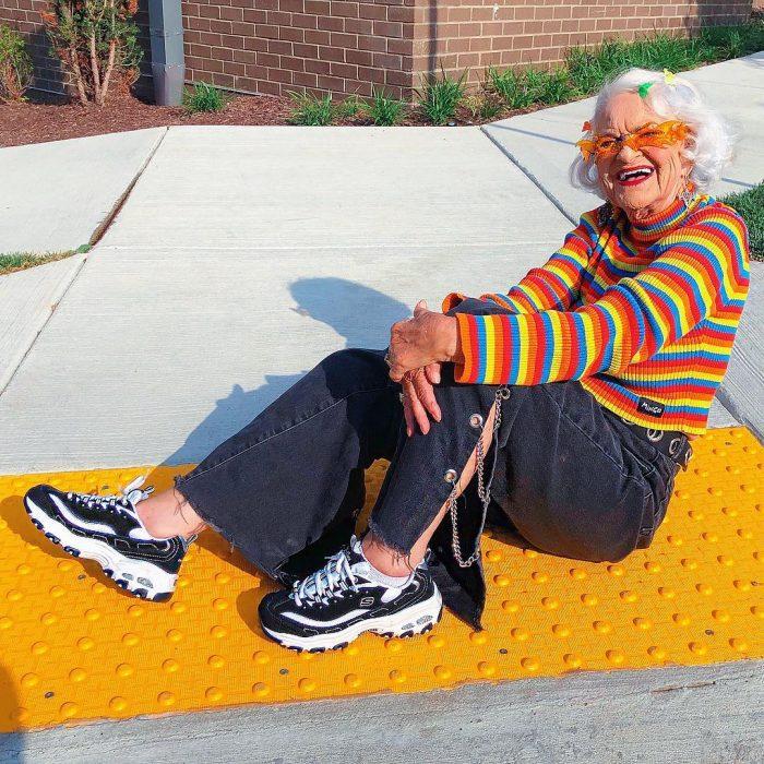 mujer en el piso y camisa de colores rayas