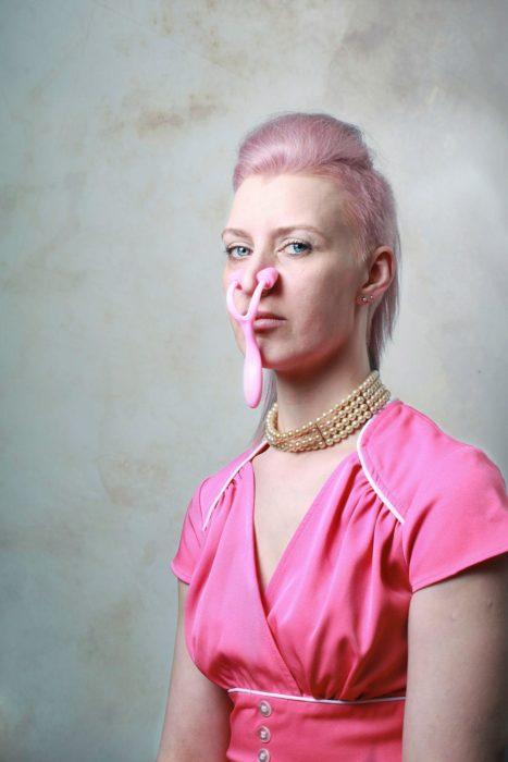 mujer con cabello rosa y aparato rosa en la nariz
