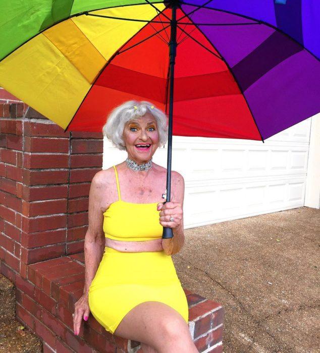 Baddie winkle posando en crop top y falda de lapiz color amarilla mientra sostiene una sombrilla