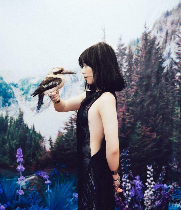 chica con vestido negro sosteniendo un ave