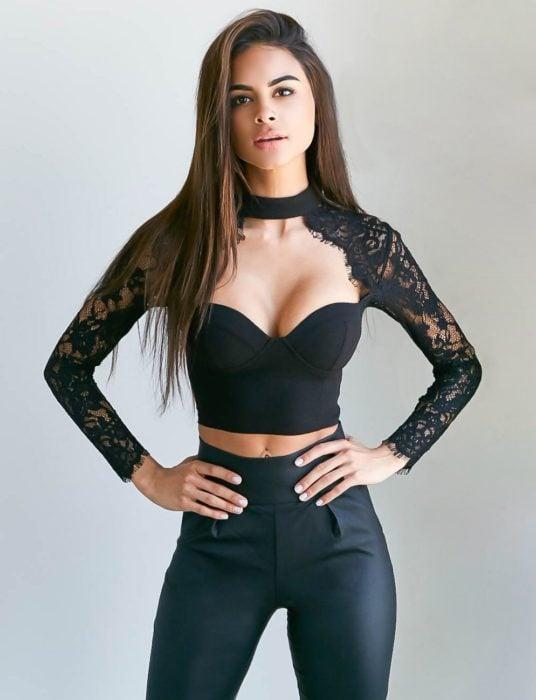 Chica usando una blusa en color negro con mangas y escote profundo