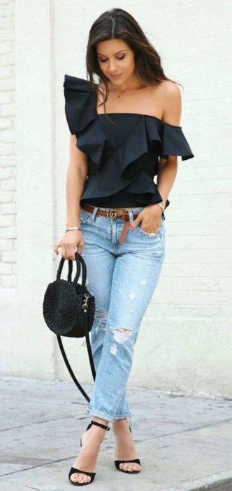 Chica usando una blusa en color negro de un hombro y con holanes