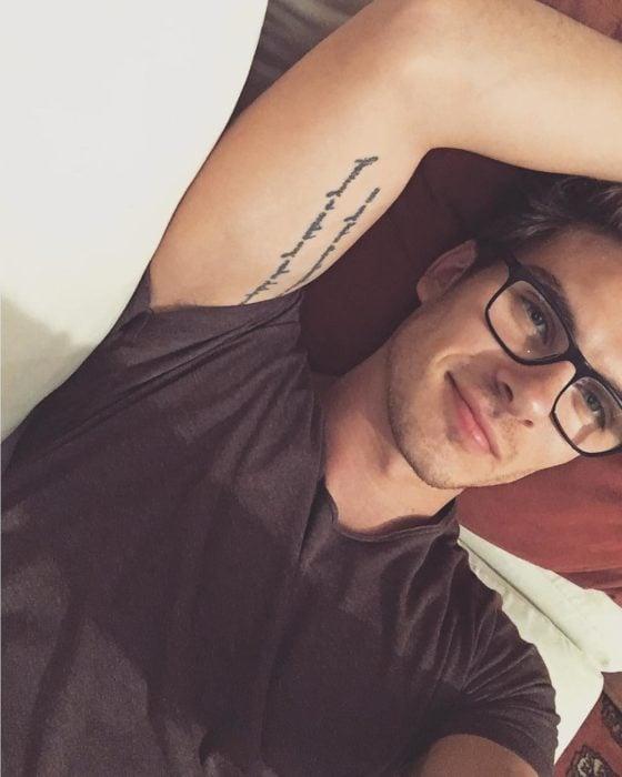 chico con tatuajes y anteojos descansando