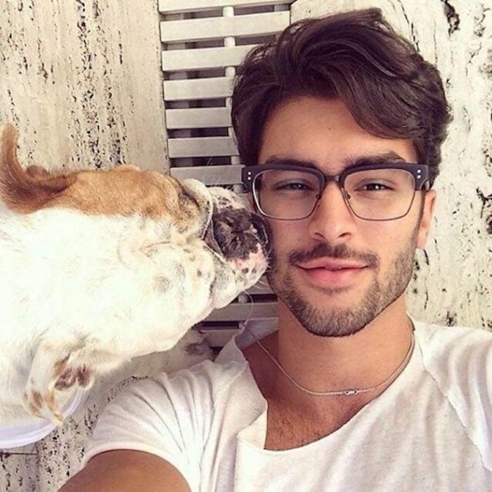 chico sonriendo con su mascota al lado